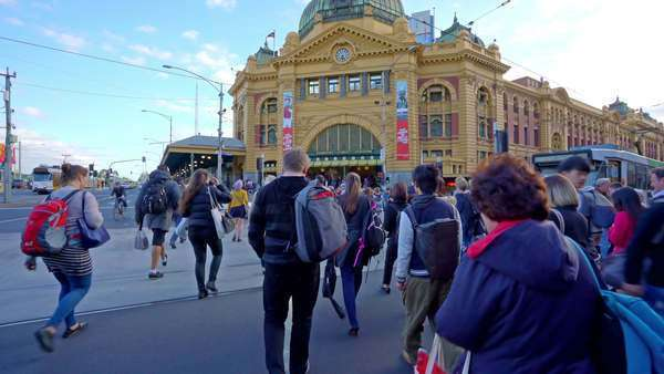 Point of view shot of people crossing a crosswalk outside Flinders Street Railway Station in downtown Melbourne, Australia, shot with gimbal stabilizer Royalty-free stock video
