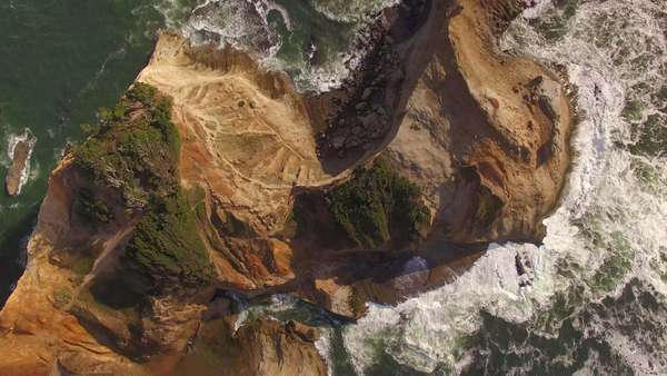 Bird's eye view of sea stack and waves along Cape Kiwanda on the Oregon coast. Rights-managed stock video
