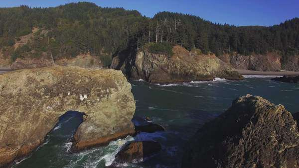 Aerial shot of Samuel H Boardman State Park along the Oregon Coast, day pan around arch way. Rights-managed stock video