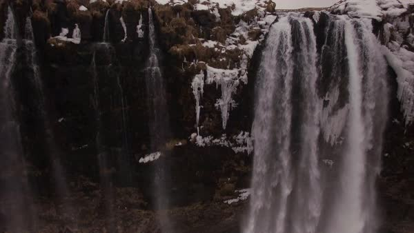 Aerial fly back over Seljalandsfoss waterfall in Iceland.  Rights-managed stock video
