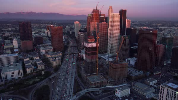 Los Angeles aerial cityscape and freeway traffic, sunset pull back. Rights-managed stock video