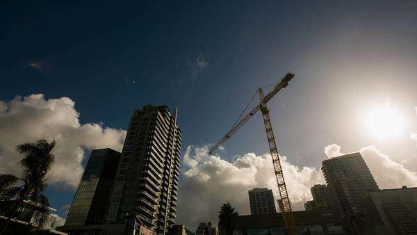Timelapse pan shot of San Diego Downtown construction crane during the day. Rights-managed stock video