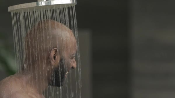 Slow motion shot of a man looking at camera while showering Royalty-free stock video