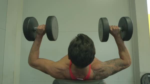 Hand-held shot of a man doing bench press with dumbbells Royalty-free stock video