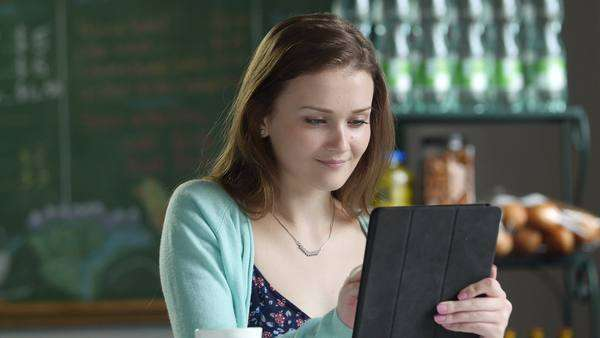 A young woman using a tablet in a cafe setting Royalty-free stock video