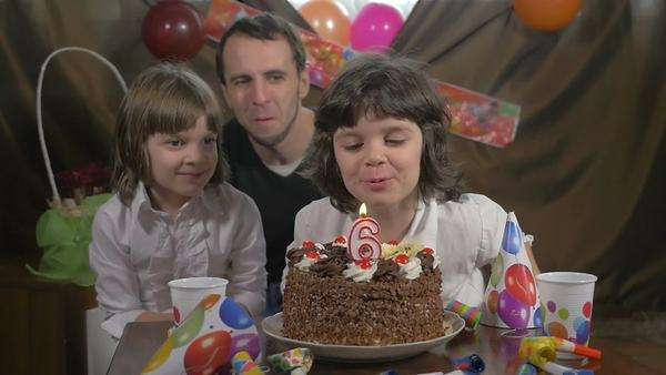 Young Beautiful Girl Blowing Candles On A Birthday Cake With Her Father And Twin Sister