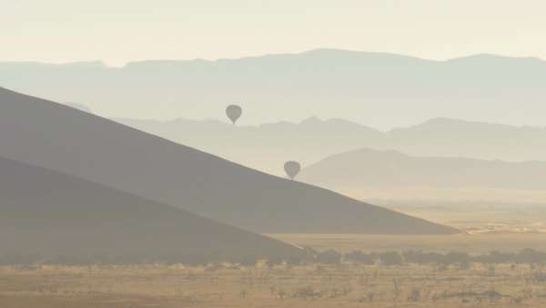 Hot air balloons flying over a wide desert landscape foggy misty morning Namibia Africa sossusvlei Royalty-free stock video