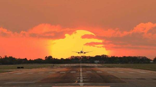 Jet plane landing at bologna airport crossing sun at the sunset Royalty-free stock video