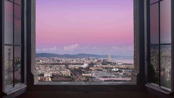Barcelona cityscape as seen from behind a window day to night timelapse at the sunset to night city lighting up panorama traffic rushing Royalty-free stock video