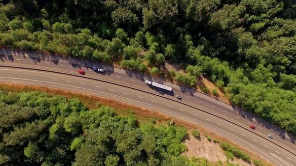 Cinematic, dizzying, spinning motion camera move, a bird's eye view of freeway traffic passing through a forest area. Royalty-free stock video