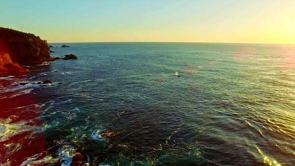 Whale spouts in the distance by a beautiful rocky bay at sunset on a summer evening Royalty-free stock video