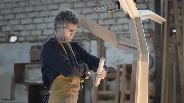 Hand-held shot of a carpenter marking an angle on a piece of wood Royalty-free stock video