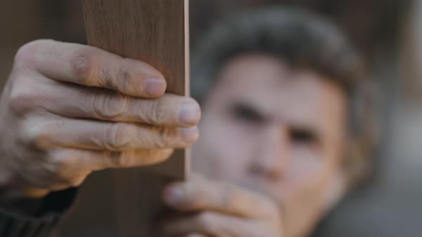 Hand-held shot of a carpenter examining a piece of wood Royalty-free stock video