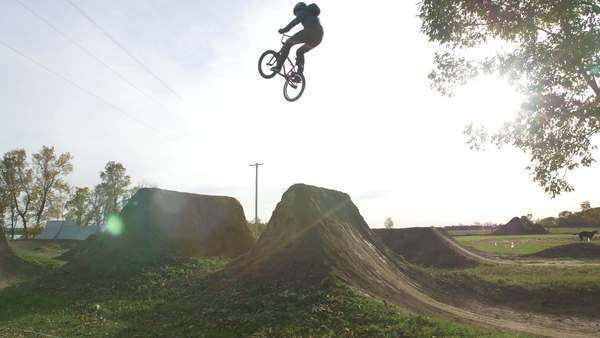 Extreme BMXer jumps Big Dirt Jump on bright sunny day Royalty-free stock video