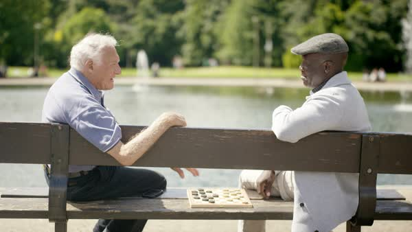 Happy senior male friends playing draughts in the park Royalty-free stock video