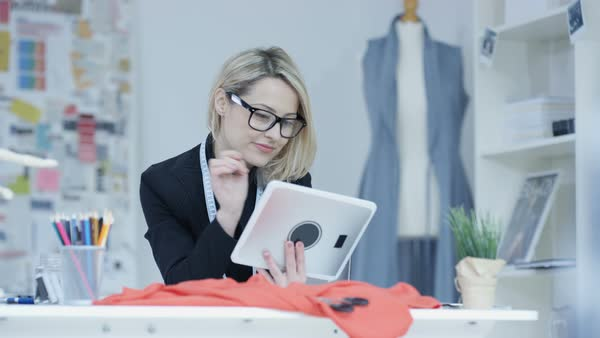 Portrait of smiling dressmaker looking at computer tablet in her studio Royalty-free stock video