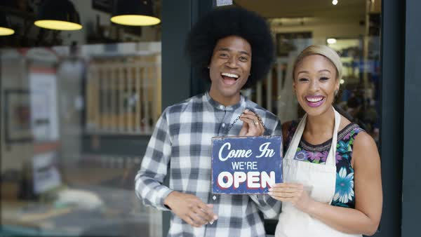 Happy cafe owner couple hold up a sign to show they are open for business. Royalty-free stock video