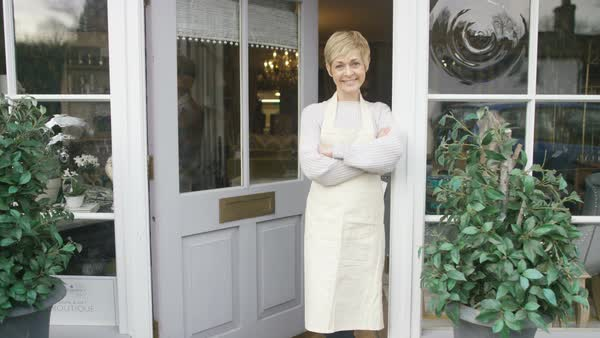 Portrait of smiling business owner standing in the doorway of her shop Royalty-free stock video