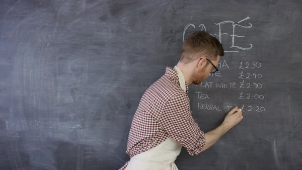 Portrait of smiling cafe worker writing drinks menu on chalkboard Royalty-free stock video