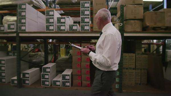 Worker in a factory or warehouse walking between rows of shelves and checking the stock. Royalty-free stock video