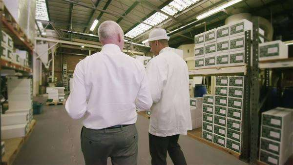 Workers in a factory or warehouse walking between rows of shelves and checking the stock. Royalty-free stock video