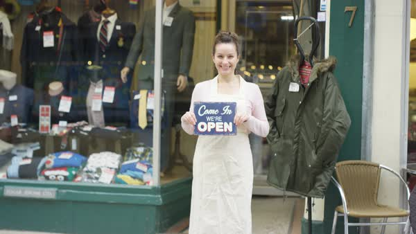 Happy shopkeeper holds up a sign to show she is open for business Royalty-free stock video