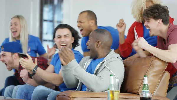 Excited group of friends watching sports game on TV celebrate when team score Royalty-free stock video