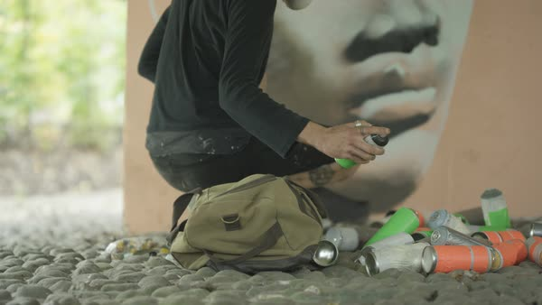 Urban artist using paint roller to cover existing graffiti on a wall Royalty-free stock video