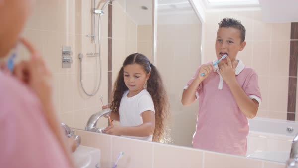 Cute young brother   sister in bathroom  looking in mirror   brushing teeth  Royalty. Happy mixed race family in bathroom brushing their teeth togethe
