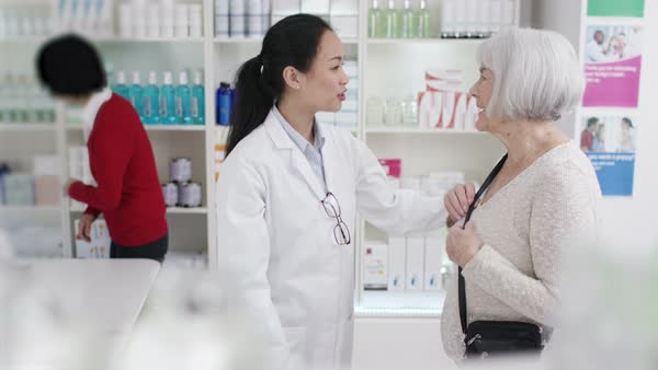 Worker in a pharmacy assisting mature lady Royalty-free stock video