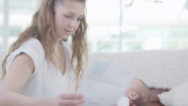 New mother with young baby, working on laptop and worrying about paying bills Royalty-free stock video