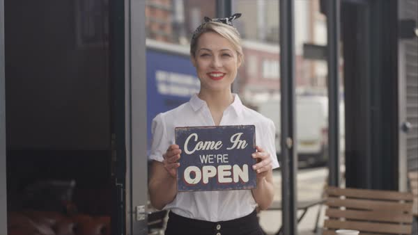Smiling bar or cafe owners hold up a sign to show they are open for businessSmiling bar or cafe owners hold up a sign to show they are open for business Royalty-free stock video