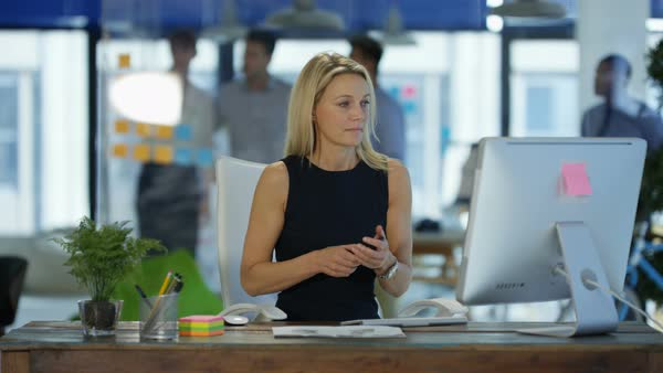Businesswoman talking on cell phone at her desk in modern office with colleagues in discussion in background. Royalty-free stock video