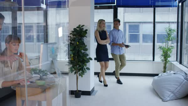 Business man and woman chatting as they walk through creative office. Royalty-free stock video