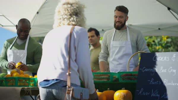 Cheerful man selling fresh fruit and veg to customers at outdoor farmers market. Royalty-free stock video