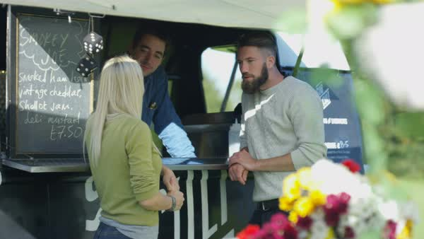 Cheerful food vendor in burger van serving customers at community event. Royalty-free stock video