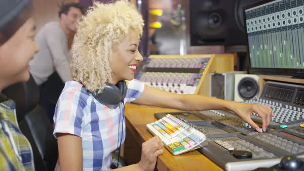 Professional team in recording studio mixing a track with male vocalist. Royalty-free stock video