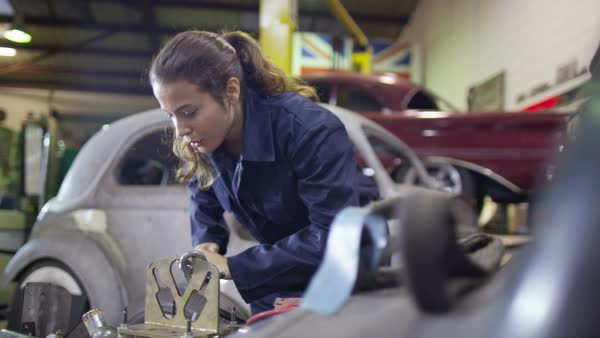 Attractive female mechanic working on car engine in garage workshop Royalty-free stock video