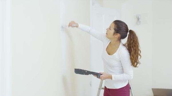 Happy attractive young woman painting a wall in new home turns to smile at camera. Royalty-free stock video
