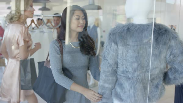 Customers shopping (including pregnant lady) and male clerk giving assistance in fashionable boutique clothing store. Royalty-free stock video