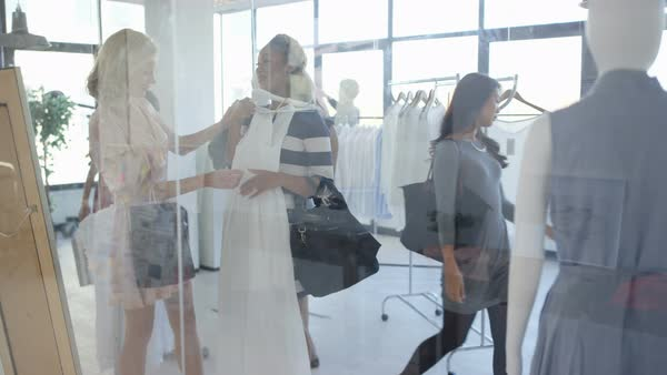 Pregnant woman shopping with a friend in fashionable boutique clothing store. Royalty-free stock video