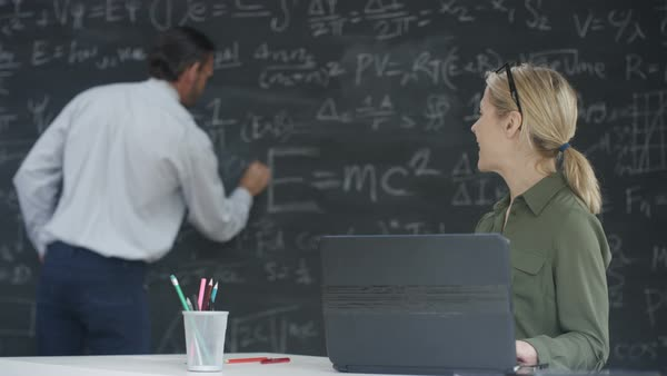 Academic man and woman working together in classroom, writing math formulas on blackboard and using laptop. Royalty-free stock video