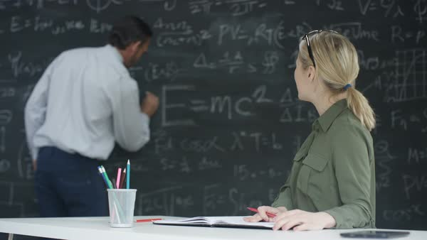 Academic man and woman working together in classroom, studying math formulas on blackboard. Royalty-free stock video