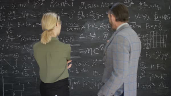 Portrait smiling academic man and woman in classroom studying math formulas on blackboard. Royalty-free stock video