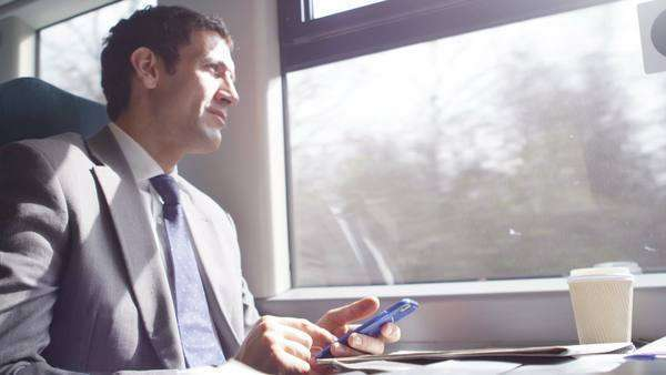 A smart businessman browsing internet on smartphone commuting into work on train. Royalty-free stock video