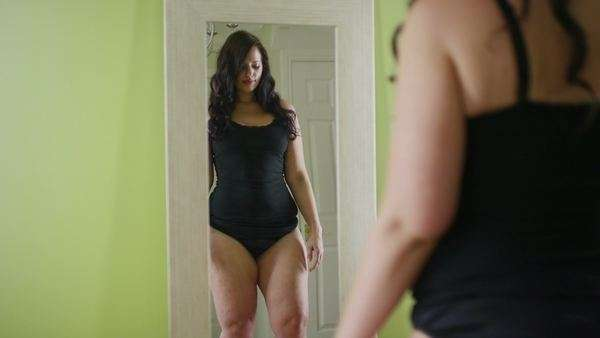 Plus size woman with positive body image stepping on scale and smiling at her reflection in the mirror Royalty-free stock video