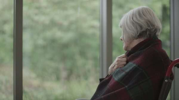 Portrait of lonely senior lady sitting by the window & looking over to her medication Royalty-free stock video