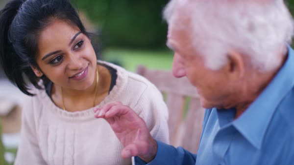 Caring young home support worker spending time with elderly gentleman in the garden. Royalty-free stock video