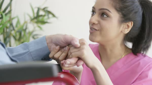 Caring young home support nurse holding the hand of elderly gentleman in a wheelchair. Royalty-free stock video