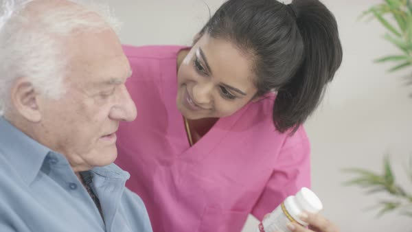 Caring young home support nurse taking care of elderly gentleman in a wheelchair. Royalty-free stock video